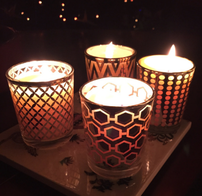 Decorative glass votives in multiple designs containing 15-hour beeswax votive candles.