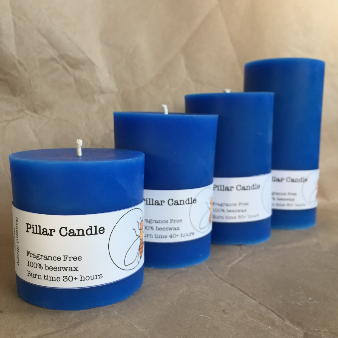 4 blue pillar candles ranging in height from 3 to 6 inches